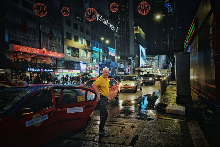 Man standing on illuminated street at night
