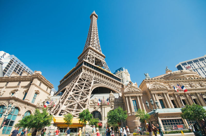 Looking up at the Eiffel Tower, Las Vegas Architecture Building Exterior Built Structure City Clear Sky Day Eiffel Tower From The Road Large Group Of People Las Vegas Las Vegas Blvd Looking Up Low Angle View Low Angle View Men Neighborhood Map Outdoors People Real People Sky Tourism Travel Travel Destinations Tree