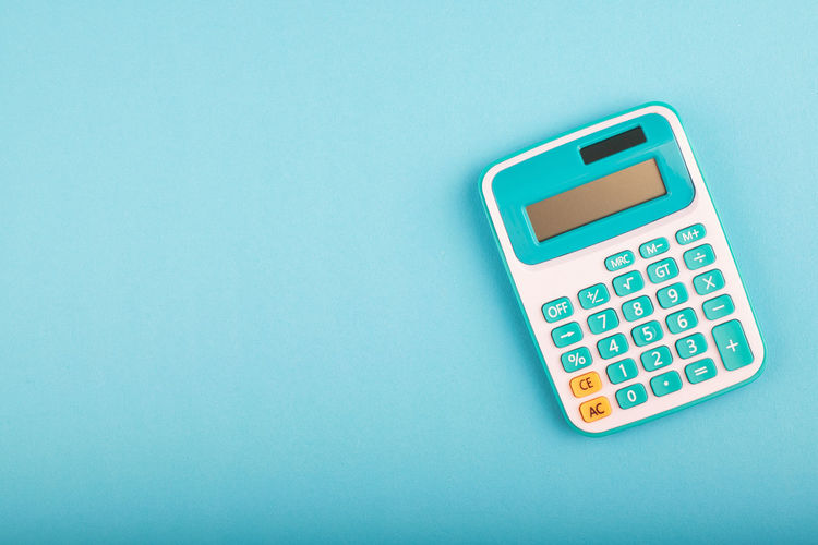 calculator on blue background. copy space for text Calculator Copy Space Blue Studio Shot Indoors  No People Still Life Number Technology High Angle View Cut Out Close-up Communication Mathematics Table Finance Business Colored Background Single Object Accuracy Blue Background Push Button Calculating Keypad Electrical Equipment