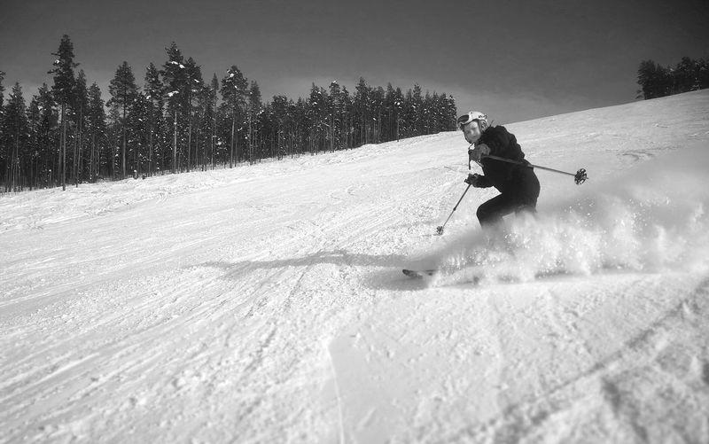 Girl skiing on snowy field against sky