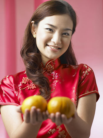chinese woman holding pair of mandarin oranges greeting Gong Xi Fa Cai Greeting Happiness Mandarin Oranges Beautiful Woman Cheongsam Chinese Ethnicity Chinese New Year Freshness Front View Happiness Holding Indoors  Lifestyles Looking At Camera One Person Orange - Fruit Portrait Qipao Red Smile Smiling Studio Shot Young Adult
