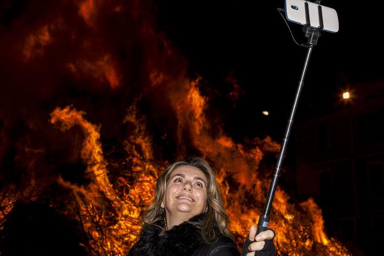 Woman taking selfie against bonfire at night
