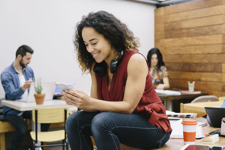 Casual Clothing Chatting Cheerful Communication Connection Coworking Creative Curly Hear Headphones Leisure Activity Mobile Phone Office Portable Information Device Real People Smiling SMS Student Studio Design Technology Typing Wireless Technology Young Adult Young Women