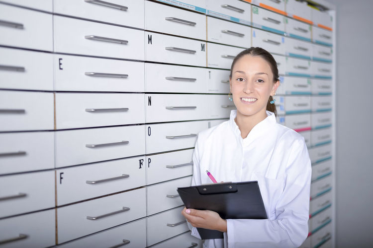 Portrait Of Smiling Young Woman Wearing Lab Coat While Standing By Cabinet