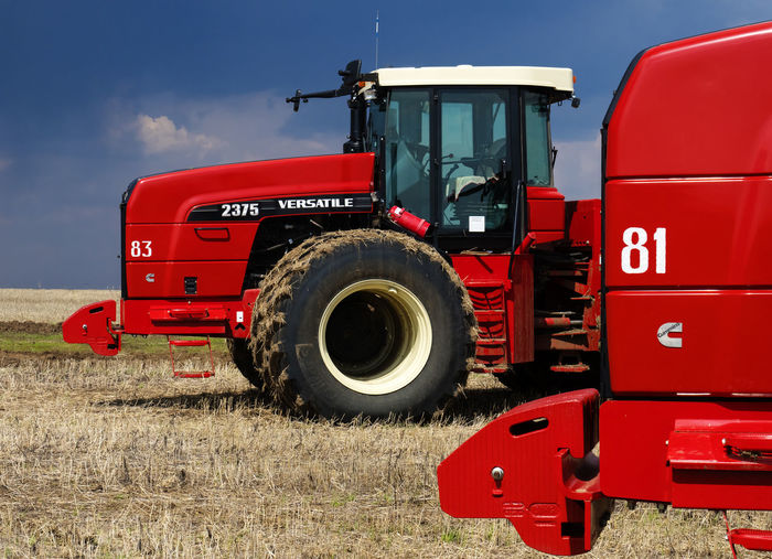Red Mode Of Transportation Land Vehicle Agricultural Machinery Transportation Tractor Truck Day Nature Land Agricultural Equipment Field Agriculture Machinery Wheel Outdoors No People Sky Sunlight Travel Tire