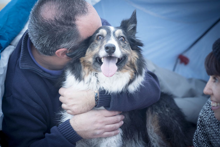 Woman Looking At Man Embracing Dog In Tent