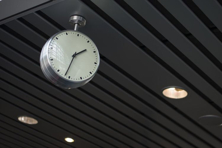 Low angle view of clock hanging on ceiling