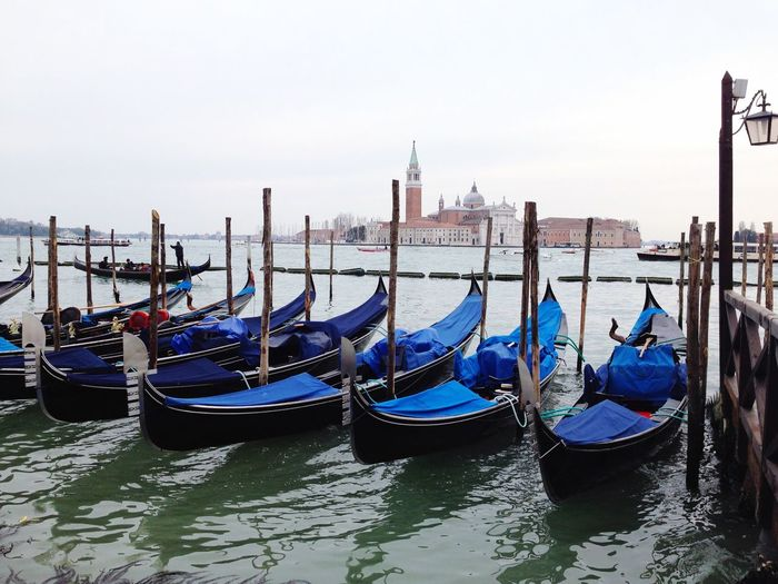 Gondolas moored in grand canal by san marco campanile against sky