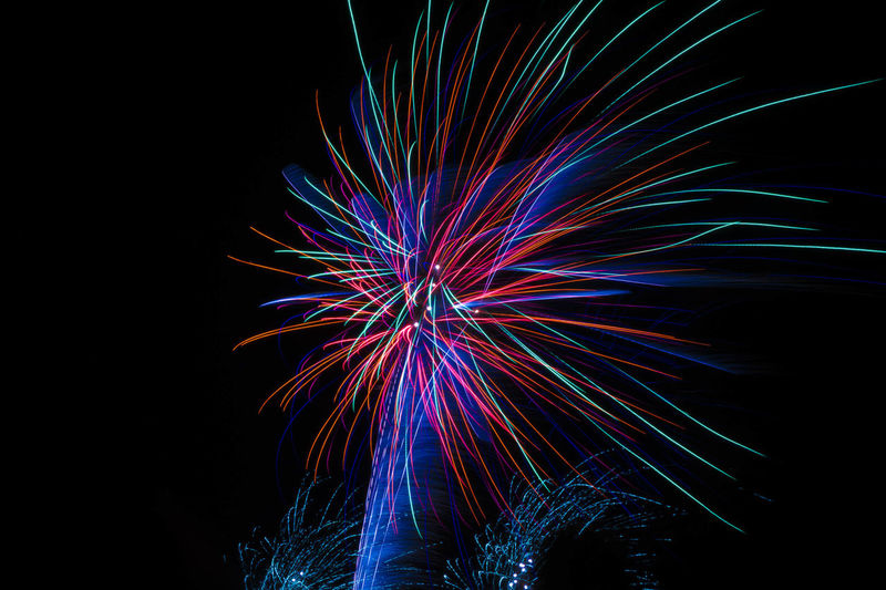 Low angle view of firework display over black background