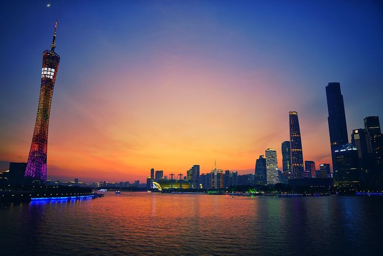 Canton tower by pearl river against sky at sunset