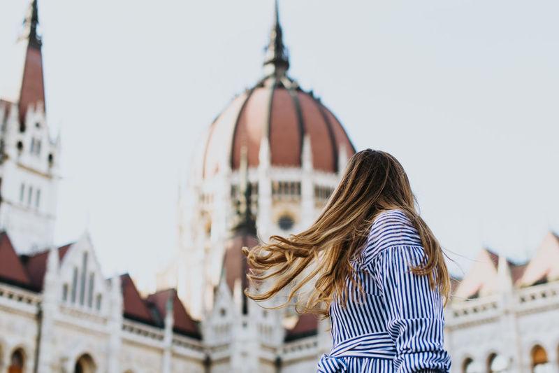 Woman walking against church in city