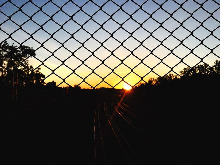 Sky Silhouette Sunset Nature Tree No People Plant Metal Railroad Track Barrier Chainlink Fence Transportation Rail Transportation Architecture Orange Color Track Sunlight Dusk Outdoors Fence