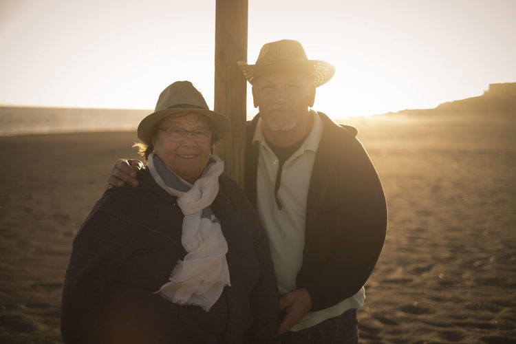 man and woman senior aged stay on the beach with beautiful backlight from sunset Adult Bonding Clothing Couple - Relationship Elderly Couple Emotion Females Lifestyles Looking At Camera Love Males  Men Nature Outdoors Positive Emotion Real People Retirement Sky Smiling Standing Sunlight Togetherness Two People Warm Clothing Women