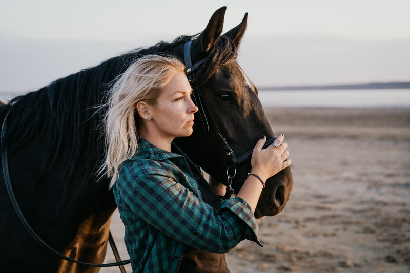 Woman with horse standing at beach