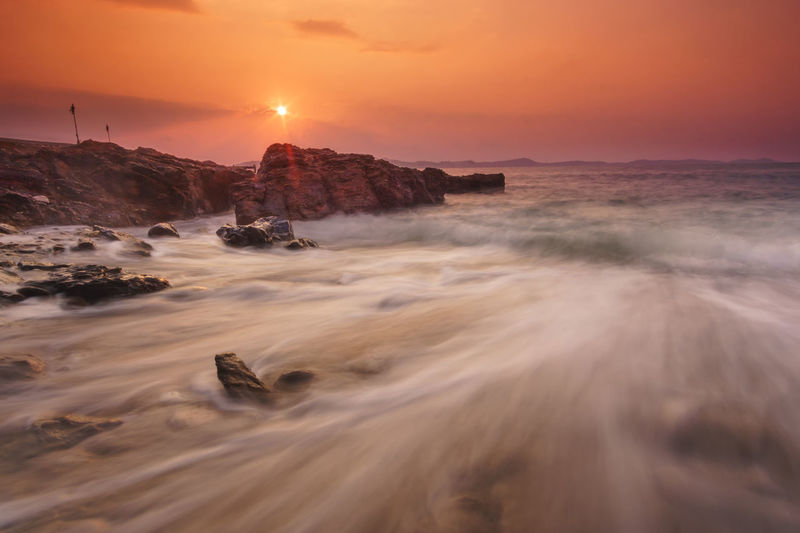 Natural seascape wave moving on the rock during sunrise ,Khao Laem Ya - Mu Ko Samet National Park, Rayong Thailand Sunset Scenics - Nature Beauty In Nature Sky Tranquility Orange Color Rock Tranquil Scene Rock - Object Solid Water Motion Nature Sea Sun Idyllic Rock Formation No People Long Exposure Outdoors Power In Nature Seascape Sunrise Wave Movement