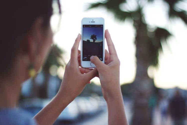 Photography Themes Smart Phone Portable Information Device Wireless Technology Mobile Phone Photographing Holding Human Hand Photo Messaging Communication Close-up Outdoors Photograph Lifestyles Vacations Real People Day Human Body Part One Person Adult
