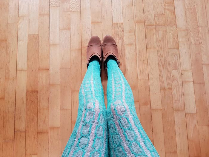 Low section of woman wearing turquoise stockings while sitting on hardwood floor