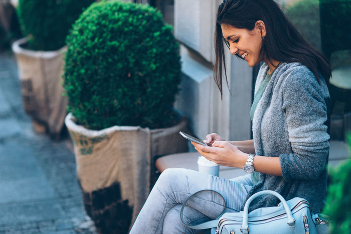 Woman Drinking Coffee In Front Of Cafe And Using Mobile Phone 20-29 Years 20s Autumn Beautiful City Coffee Dark Hair Horizontal Lifestyle Mobile Phone Shopping Woman Young Cute Drink Long Hair Looking One Person Outdoors Smiling Springtime Take Away Coffee Teenager Texting Young Adult