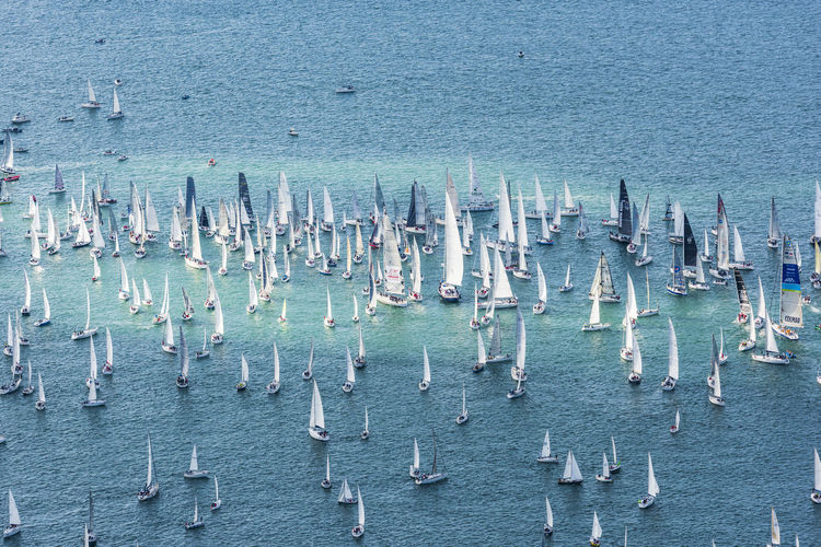 High angle view of sailboats in sea against building