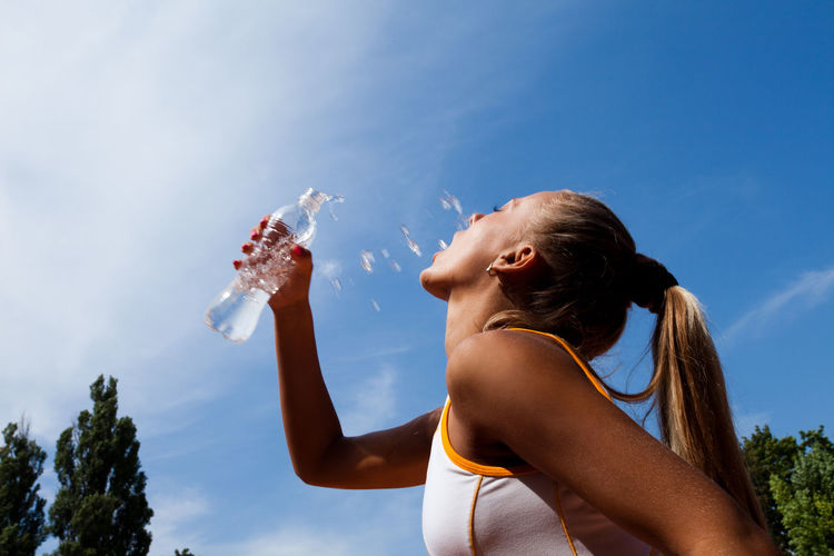 Young sporty woman drinking water from a bottle against the blue sky Sky One Person Refreshment Lifestyles Drink Nature Bottle Holding Long Hair Young Adult Hairstyle Adult Women Drinking Day Food And Drink Container Real People Water Bottle  Hair Outdoors Glass