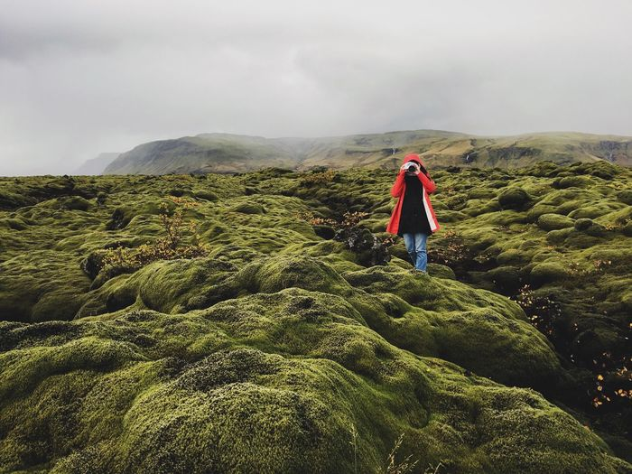 Woman Photographing With Camera While Standing On Lava Field