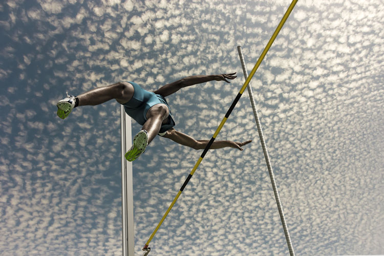 Low Angle View Of Male Athlete High Jumping Against Sky