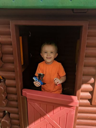 Portrait of smiling boy holding toy in hut