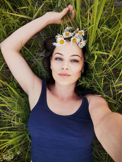 Portrait of beautiful young woman with flower petals on grass