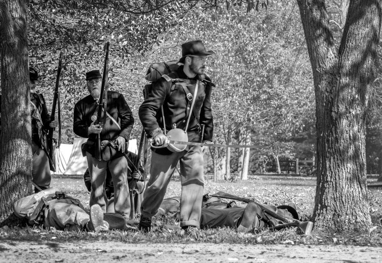 confederate and union soldier recreate a battle during a civil war event in Michigan USA Adults Only Civil War Event North And South Army Soldier Blacka Nd White Confederate Soldiers Full Length Guns Mammal Men Military Military Uniforms Nature Outdoors People Real People Reenactors Tree Union Soldiers Uniroms War Weeopons