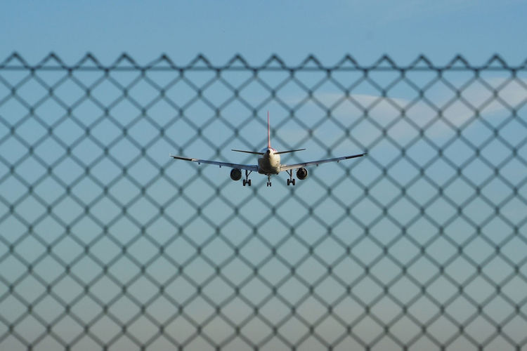 Close-up of airplane on chainlink fence against clear blue sky