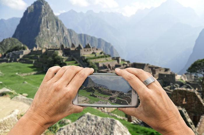 Female photographer with smartphone takes a picture of the Machu Picchu ruins Beauty In Nature Close-up Communication Day Holding Human Body Part Human Hand Landscape Machu Picchu Men Mobile Phone Mountain Mountain Range Nature One Person Outdoors Peru Photographing Portable Information Device Real People Scenics Smart Phone Travel Travel Destinations Wireless Technology