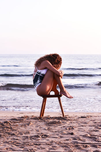 Full Length Side View Of Woman Sitting On Chair At Beach Against Clear Sky