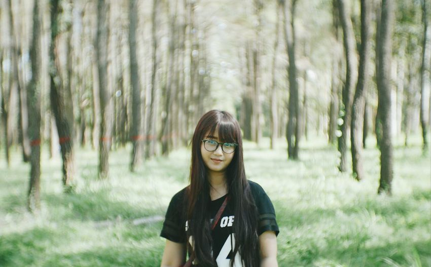 Portrait of young woman wearing eyeglasses at forest