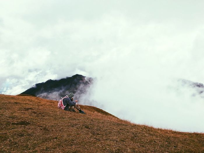 Man Sitting On Mountain Against Sky During Foggy Weather