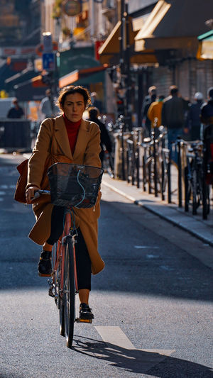 Portrait of woman riding bicycle on road in city