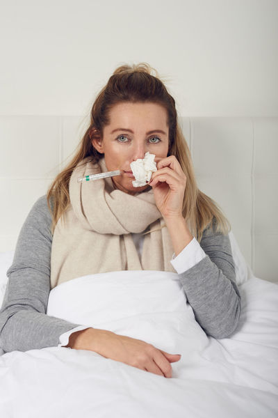 Sick woman taking her temperature Bed Copy Space FLU AND COLD SEASON Woman Bedroom Best Ager Blond Fever Fevereiro Healthcare And Medicine Human Nose Ill Illness Looking At Camera Middle-aged One Person Paper Tissue Seasonal Sick Sickness Sneezing Thermometer