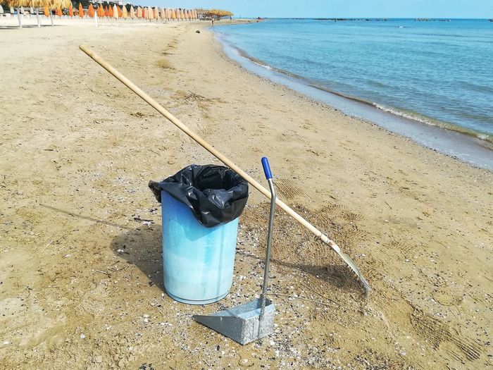High angle view of garbage bin with rake at beach