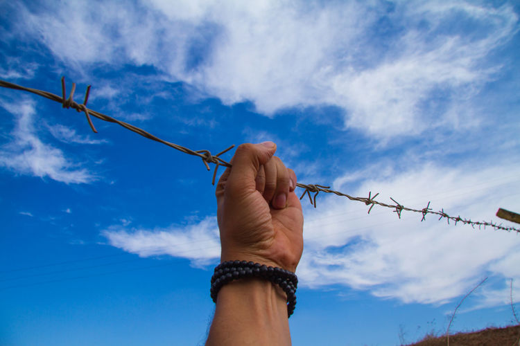 Cropped hand of man holding barbed wire against blue sky