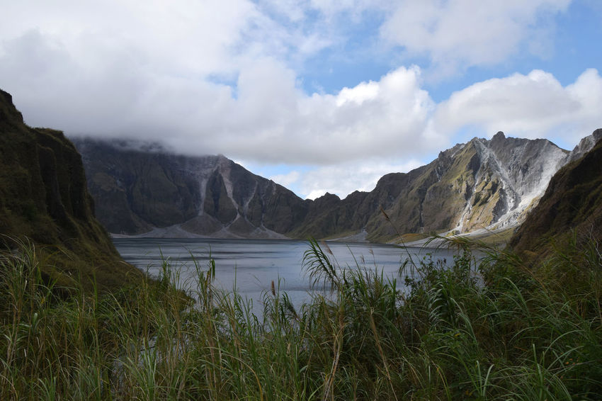 Mount Pinatubo crater lake as seen from half way down to water level Beauty In Nature Blue Calm Cloud - Sky Countryside Crater Crater Lake Day Growth Idyllic Lake Majestic Mountain Nature Philippines Remote Remote Location Scenics Sky Surrounding Tranquil Scene Tranquility Volcano Volcano Crater Water