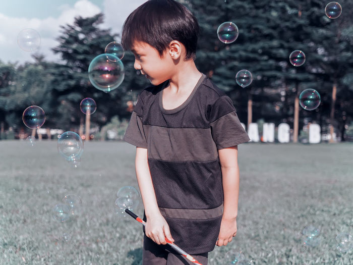 Close-up of boy blowing bubbles in park