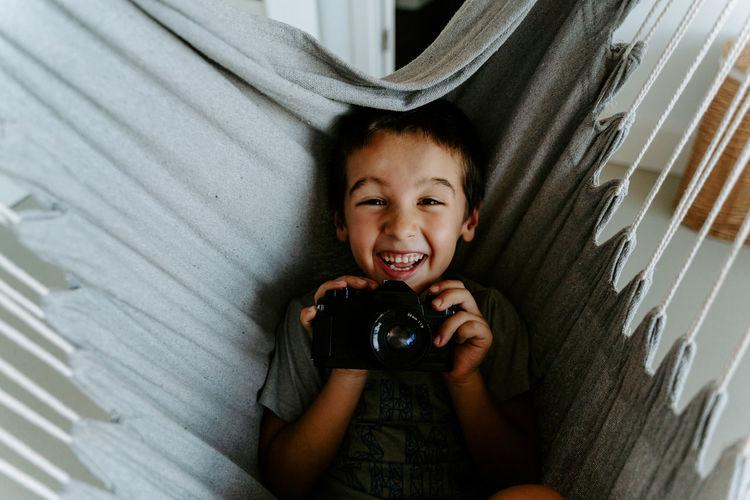 Portrait of happy boy photographing