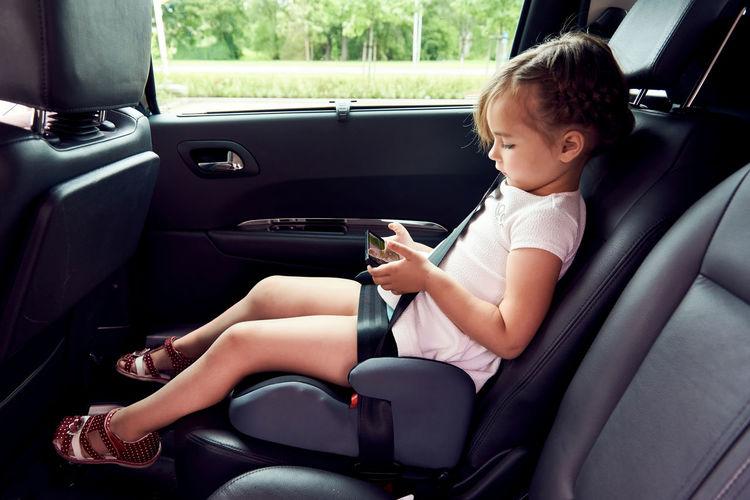 Girl holding mobile phone in car