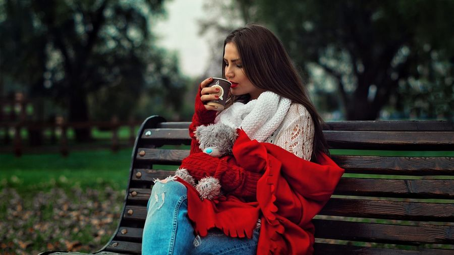 Young Woman Having Drink While Sitting On Bench In Park