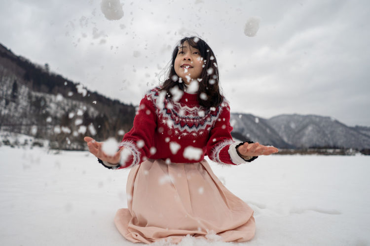 Smiling woman playing while kneeling on snow