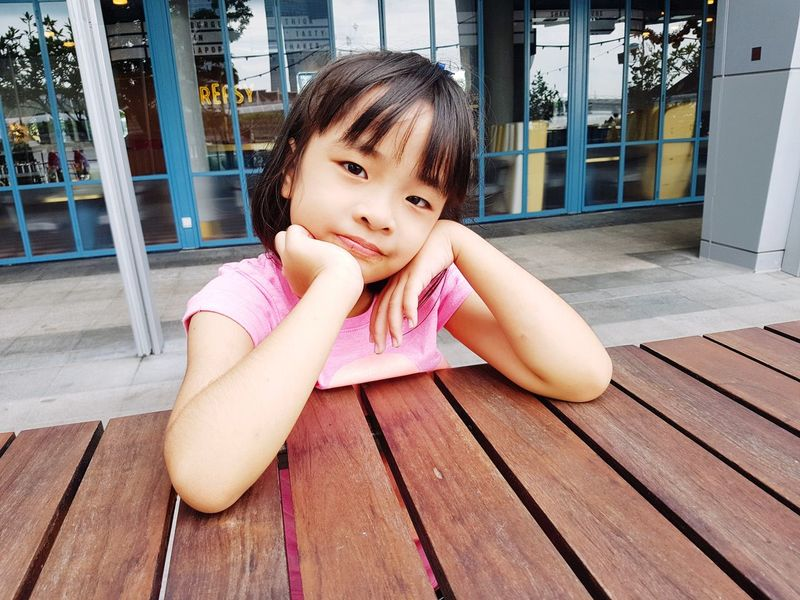 Waiting EyeEmStreetshots Eyeemgirl Girl Portrait EyeEm Selects Childhood Child Close-up Building Exterior Built Structure Children Hand On Chin Head And Shoulders Thoughtful Pensive Attractive Asian  Leaning On Elbows Bangs