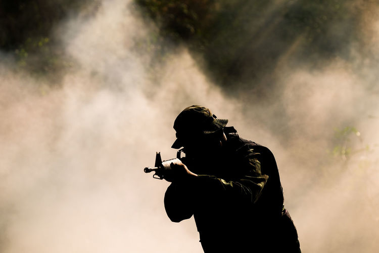Silhouette soldier against smoke outdoors
