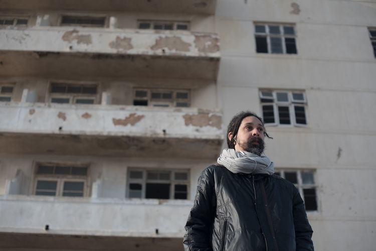 Low angle view of thoughtful man standing against old building