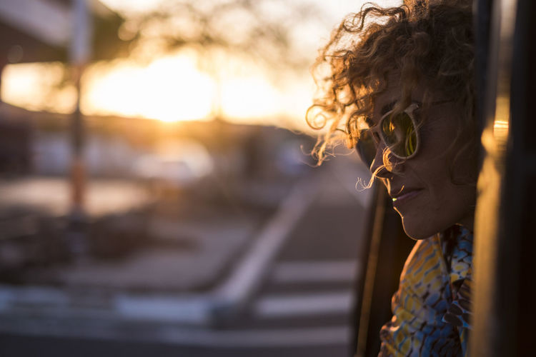 Close-Up Of Woman Wearing Sunglasses Looking Away During Sunset
