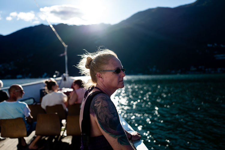 Mature woman standing on boat deck against mountain