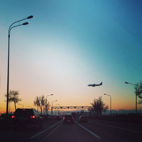 Flying Transportation Mid-air Airplane Mode Of Transport Street Light Sunset Travel Road Air Vehicle Journey Outdoors Silhouette Sky Stoplight Clear Sky Road Sign No People Day